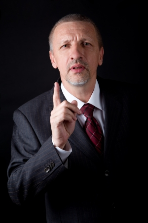 dissatisfied: Dissatisfied mature businessman showing disapproval gesture