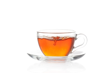 Cup of hot black tea with air bubbles isolated on white photo