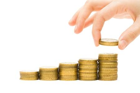 cash money: Concepto de dinero - mano poniendo monedas en pilas de dinero de oro