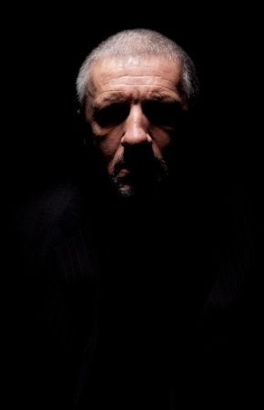 evil eyes: Spooky grey haired mature man with black-out eyes
