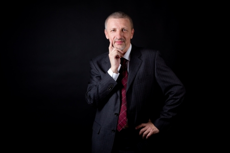 Smiling businessman holding his hand on chin Stock Photo