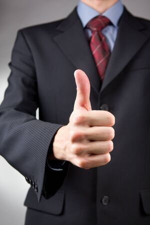 Businessman gesturing thumbs up on neutral background photo