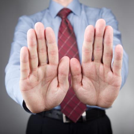 Man gesturing stop hand sign  Neutral background