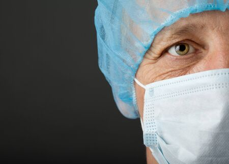 Doctor s face with mask and cap on grey background photo
