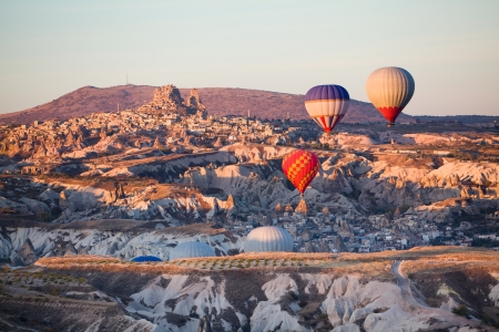 Balloons over Uchisar castle in Cappadocia at sunrise, Turkey photo