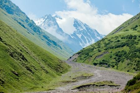 tien shan: Stony road and white mountain peak, Tien Shan, Kyrgyzstan Stock Photo