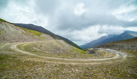 unsurfaced road: Turn of the serpentine road, Tien Shan mountains, Kyrgyzstan