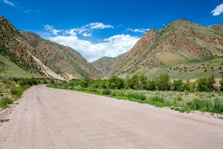 unsurfaced road: Mountain road in sunny day, Kyrgyzstan