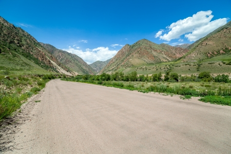 unsurfaced road: Wide country road in mountains, Kyrgyzstan