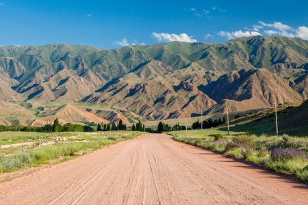tien shan: Wide country road in Tien Shan mountains, Kyrgyzstan Stock Photo