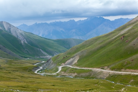Winding road in mountains in Kyrgyzstan Фото со стока