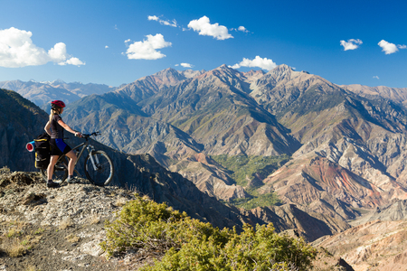 Bicycle traveler with loaded bike standing at cliff and enjoying view of mountains. Pontic mountains, Turkey Фото со стока