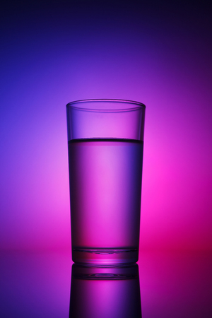 Glass of water lit with abstract pink and purple backlight