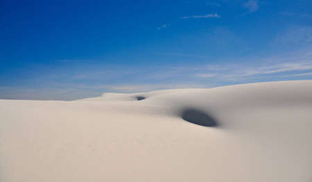 White sands national monument is one of the most beautifull parks in the USA  White sand dunes with strange curves make some incredible sights in this case liek a belly button The blue sky around it makes it additionally dramatical photo