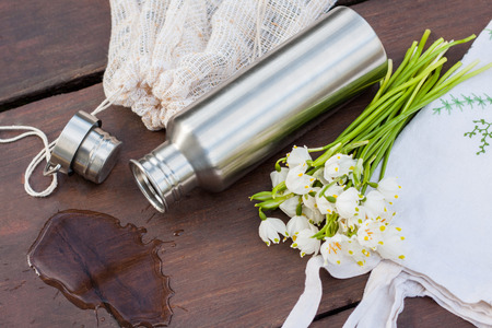 A look into zero waste lifestyle - everyday items. A produce bag repurposed from old curtains, a durable stainless steel water bottle, all in one solid shampoo and balsam in a reusable tin container.
