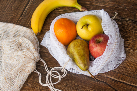 Zero waste, plastic free recycled textile produce bag for carrying fruit (apple, orange, pear and a banana) or vegetables, a wooden surface. Bags are made with a sewing machine out of old curtains. Standard-Bild