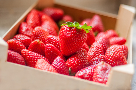Fresh and sweet ripe red strawberries from Spain on the kitchen counter. Stored in a natural wooden plastic free box or case.