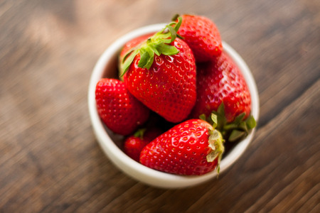 Fresh and sweet ripe red strawberries from Spain on a glass table outdoors. Served as a healthy snack or dessert in a small white ceramic bowl. Standard-Bild