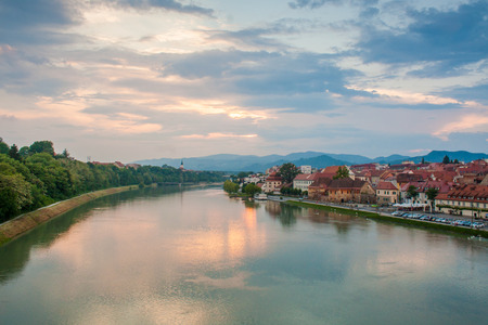 View of Maribor, Slovenia, Central Europe and the Lent area. Photo taken from Glavni most - bridge over the river Drava. Evening sky after sunset over colourful houses and a church in the distance.