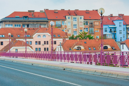 Colourful houses and high buildings in the city or town of Maribor, Slovenia, Central Europe. Streetlights on a main bridge with a purple fence leading towards the city, empty road. Standard-Bild