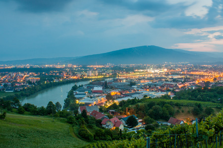 The magnificent view of the city of Maribor, Slovenia, Central Europe from Meljski hrib. Pohorje hills in the background, river Drava and street lights shining brightly on a stormy spring night.
