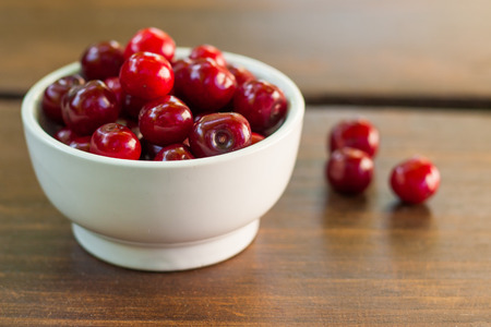 Bright red ripe freshly picked early sweet cherries in may on a dark wooden table. Fruits with stalks in a small white ceramic bowl. Standard-Bild