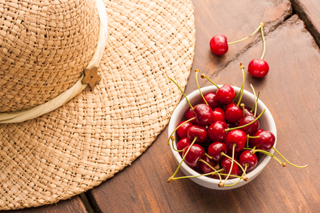 Bright red ripe freshly picked early sweet cherries in may on a dark wooden table. Fruits with stalks in a white ceramic bowl and a summer straw hat as decoration.