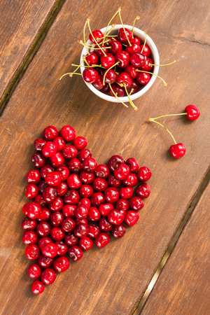 Bright red ripe freshly picked early sweet cherries in may on a dark wooden table. Fruits with stalks in a white ceramic bowl, single cherries forming the shape of a heart - symbol of love.
