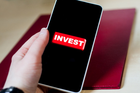 Bright red invest button on a black phone screen, holding in hand. Making money on your smartphone.