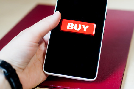 Buy button on a phone screen. Bright red buy button on a black phone screen, holding in hand. Making money on your smartphone.