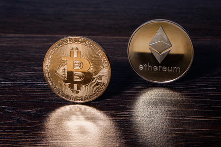 Golden Bitcoin and ethereum crypto currency physical real metal coins reflected on a dark wooden surface.