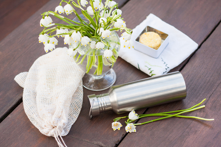 A look into zero waste lifestyle - everyday items. An embroidered textile shopping bag, a produce bag repurposed from old curtains, a durable stainless steel water bottle and a cute bouquet of flowers Standard-Bild