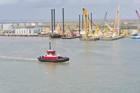 tug boat inside the port with oil rigs in the surroundings