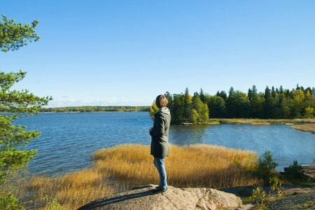 Man looking at sea in autumn forest Stock Photo
