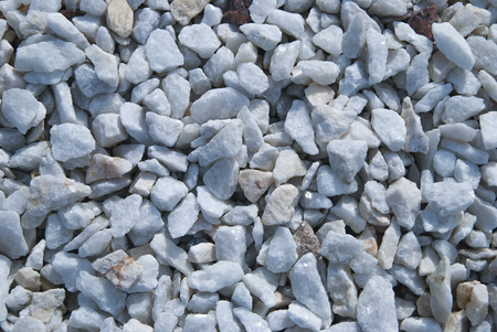 Little White Minerals Rocks  Background. Gravel Stones at sunny day. Decorative elements on the street Imagens