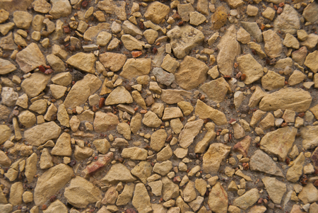Little Grey Brown Minerals Rocks  Background. Gravel Stones at sunny day. Decorative elements on the wall Imagens