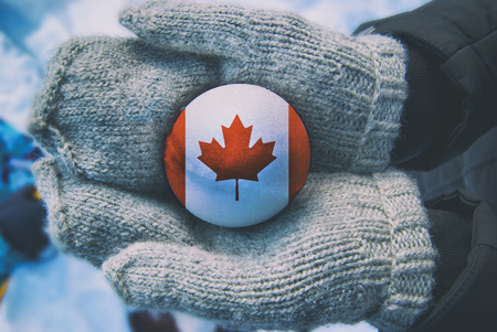 Snowball with a flag of Canada in a woman hands in mittens. Winter sunny day Imagens