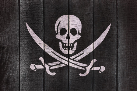 Calico Jack Pirate Flag on a wooden backgound. Pirates flags on wood texture