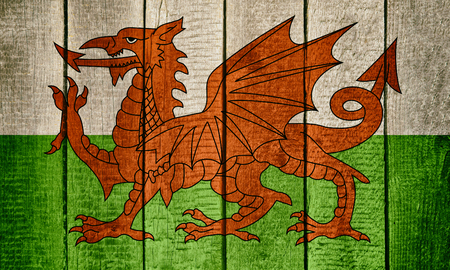 Flag of Wales on a Wooden background. A Red Dragon on a green wood texture Imagens