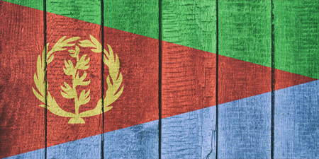 Old  wooden table texture background top view  with a National Flag of Eritrea. Eritrean Flags image. Imagens