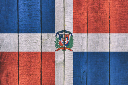 Old  wooden table texture background top view  with a National Flag of Dominican Republic. Dominicanian Flags image.