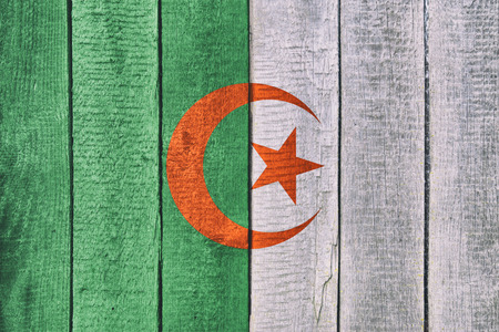 Old  wooden table texture background top view  with a National Flag of Algeria. Algerian Flags image.
