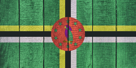 Old  wooden table texture background top view  with a National Flag of Dominica. Dominican Flags image. Imagens