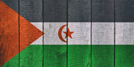 Old  wooden table texture background top view  with a National Flag of Western Sahara. West Sahara Flags image.