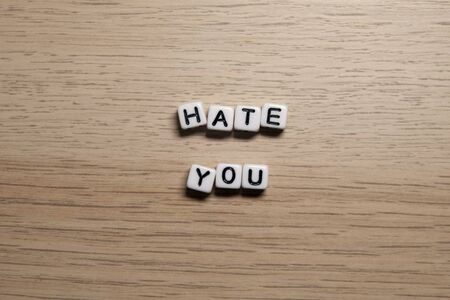 Word HATE YOU in white cubes on light wooden background for your design templates