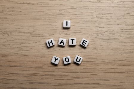 Word I HATE YOU in white cubes on light wooden background for your design templates.
