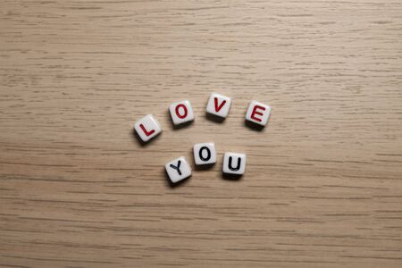 Word LOVE YOU red letters in white cubes on light wooden background Imagens