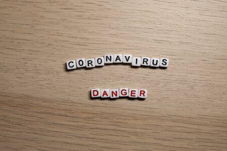 the word CORONAVIRUS DANGER in white cubes on a light wooden background. Coronavirus design template.
