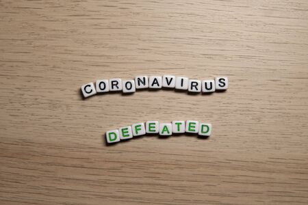 the word CORONAVIRUS DEFEATED in white cubes on a light wooden background. CoronaVirus design template