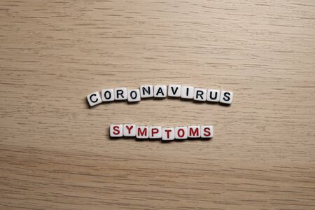 the word CORONAVIRUS SYMPTOMS in white cubes on a light wooden background. Coronavirus design template. Imagens